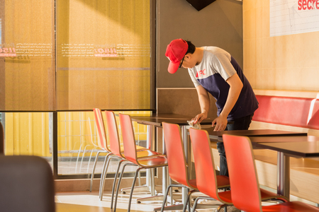Nonthaburi, Thailand - March, 07, 2018 : Unidentified name man staff worker is cleaning the dining table in the Kentucky Fried Chicken (KFC) restaurant at Nonthaburi, Thailand