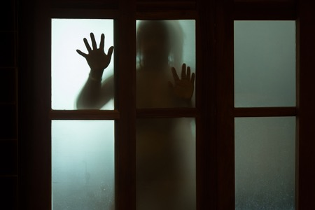 Horror woman behind the window glass in black and white. Blurry hand and body figure abstraction.Halloween background