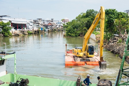 Chanthaburi, Thailand - April, 27, 2018 : Barge carrying heavy construction crane being dredging in Chanthaburi Canal at Chanthaburi, Thailand