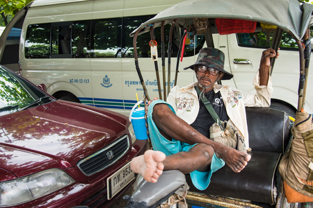 Lop Buri, Thailand - April, 29, 2018 : Unidentified name old man tricycle bicycle taxi waiting for customers on the street Lop Buri railway station at Lop Buri, Thailand