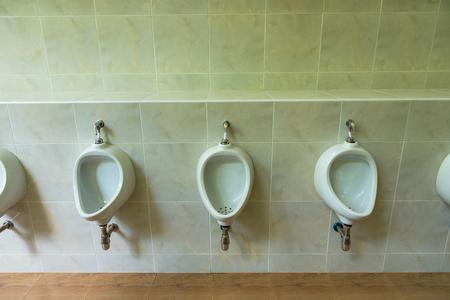 Closeup of three white urinals in men's bathroom design of white ceramic urinals for men in toilet room 免版税图像