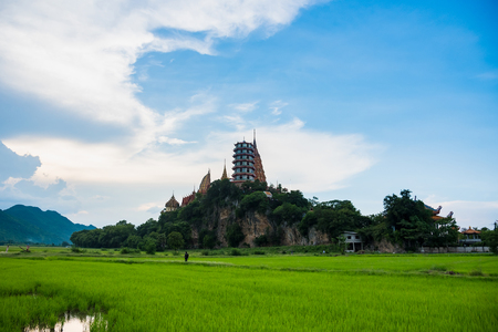 Kanchanaburii, Thailand - May, 13, 2018 : Wat thum sue temple and rice field in sunset time at kanchanaburi thailand most popular religion traveling destination