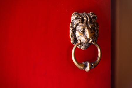 Old rusty lion door knocker on bright red painted door Stock Photo