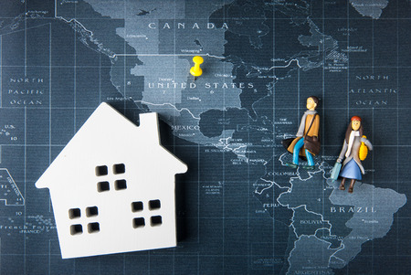 Wooden white house model and doll man and woman toy evacuate on the world map pin to United States of america.Real estate concept, New house concept. Stock Photo