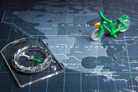 Compass and green bicycle toy on the world map.Business travel world wide system concept