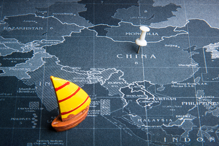 Yellow sailboat on the world map pin to China countries.Business transportation system concept