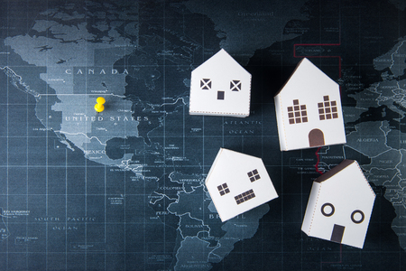 Paper white house model on the world map.Real estate concept, New house concept