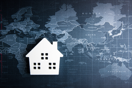 Wooden white house model on the world map.Real estate concept, New house concept