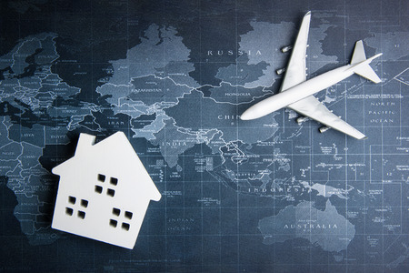 Passenger plane and wooden toy white house on the world map.Business transportation system concept Stock Photo
