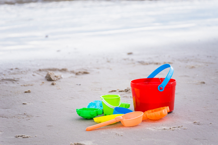 Children's beach toys - buckets, spade and shovel on sand on a sunny day Standard-Bild