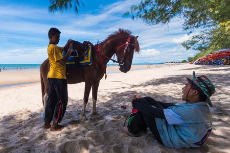 Prachuap Khiri Khan,Thailand - June, 03, 2018 : Unidentified name Boy horse owners for rent sitting in the shade of a tree on the beach at Hua Hin beach Prachuab Khirikhan, Thailand Editorial