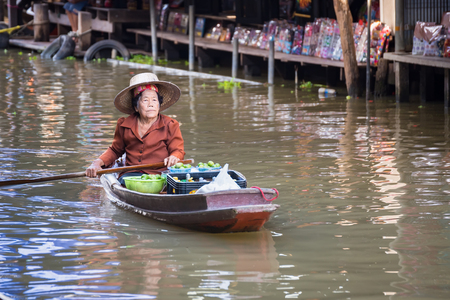 Ratchaburi,Thailand - June, 02, 2018 : Unidentified old woman vendor fruit floats in a boat at Damnoen Saduak floating market Ratchaburi, Thailand.