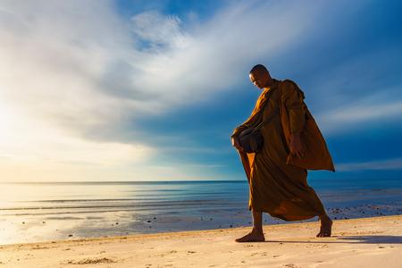 Prachuap Khiri Khan,Thailand - June, 03, 2018 : Unidentified name buddhist monk was walking alms offering food in the morning on the beach at Hua Hin Beach Prachuab Khirikhan, Thailand.