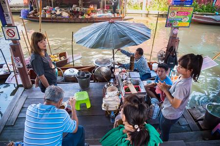 Ratchaburi,Thailand - June, 02, 2018 : Unidentified name tourist sitting eat food on a riverbank canal in Damnoen Saduak floating market at Ratchaburi,Thailand