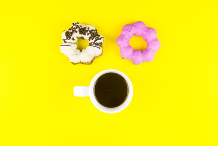 Donut made at home with White Coffee Cup of Espresso on yellow background.Breakfast in the morning rush hour.High energy foods to work.Foods with very high calories, sugars and caffeine
