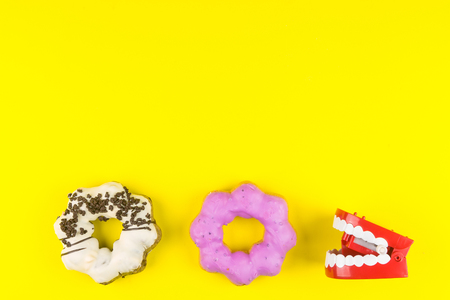 Donut made at home and red plastic wind up chattering teeth on yellow background same concept with pacman game.High energy foods to work.Foods with very high calories, sugars Stok Fotoğraf