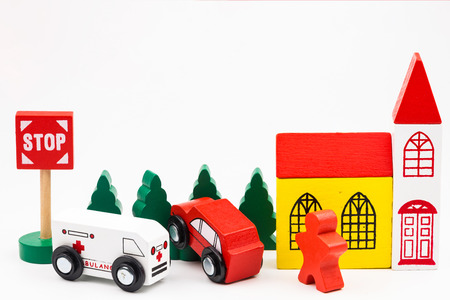 Wooded toy car are crashed. Accident road traffic with wooden toy cars in the town on white background, safety and traffic regulations concept, backgrounds.Transportation system concept Stock Photo