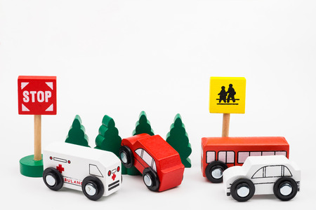 Wooded toy car are crashed. Accident road traffic with wooden toy cars in the town on white background, safety and traffic regulations concept, backgrounds.Transportation system concept Stok Fotoğraf