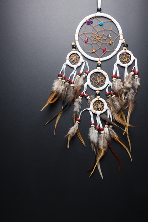 Dream catcher with feathers threads and beads rope hanging spiritual folk american native indian amulet isolated on black background.Copy space for text.Concept prevent evil in Halloween