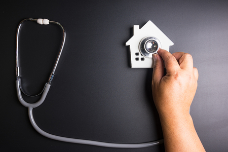 House model with stethoscope isolated on black background.Indicates the health of the house. Reklamní fotografie