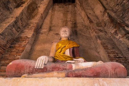 Old buddha statue with old wall brick of Wat Nakhon Luang Tample,Prasat Nakhon Luang in Ayutthaya,Thailand