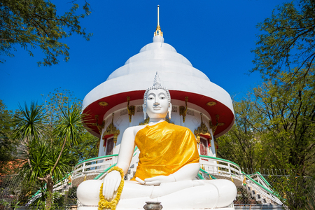 Buddha statue on hill white buddha statue on green mountain with tree background.Thailand