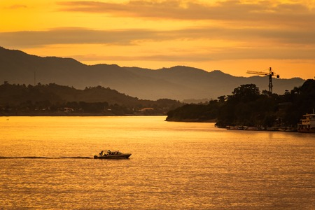 The ship is sailing in the Mekong River in In the morning, the sunrise in the Golden Triangle, Chiang Rai, Thailand