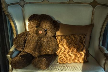 Teddy bear sit alone, Teddy Bear sitting on chair with sun light morning.Thailand