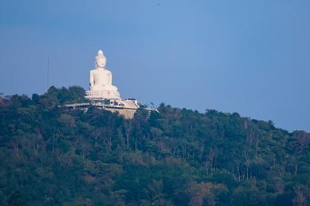 Buddha statue on green mountain and blue sky.Phuket.Thailand Фото со стока