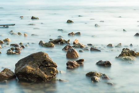 Waves on stone beach waters edge abstract sea background.Thailand