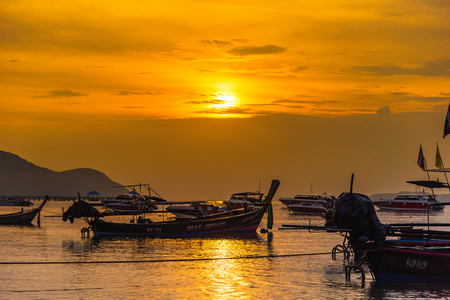 Phuket, Thailand - March, 31, 2019 : Sunrise above Tour boat on the beach. morning light shines up from the edge of the sea. A reflection on Tour boat parked on Rawai beach.Phuket, Thailand Éditoriale