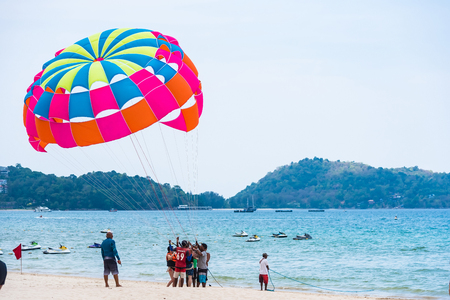 Phuket, Thailand - March, 29, 2019 : Unidentified name tourist sea parasailing water.Flying on a parachute behind a boat on a summer holiday by the sea at Patong beach in Phuket, Thailand