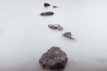 Photo Black and White of Long Exposure Photography Waves on stone beach waters edge abstract sea background.Thailand.