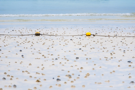 A string of yellow buoys on the beach for safety zoning in the sea.Thailand.