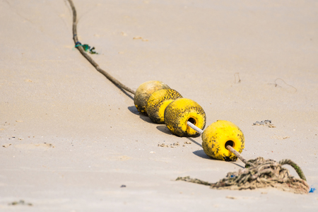 A string of yellow buoys on the beach for safety zoning in the sea.Thailand Archivio Fotografico
