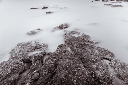 Foto en blanco y negro de la fotografía de larga exposición Olas en el borde de las aguas de la playa de piedra fondo abstracto del mar. Tailandia. Foto de archivo