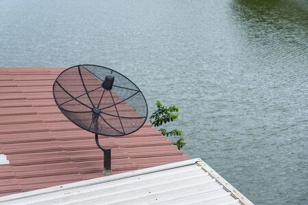 Satellite dish on the roof of a wooden house.Satellite dish is a device for receiving TV signals Banco de Imagens