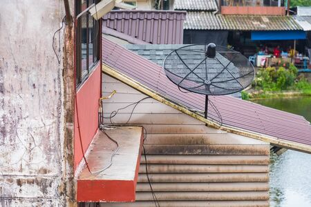 Satellite dish on the roof of a wooden house. Satellite dish is a device for receiving TV signals Banco de Imagens
