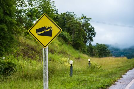 Yellow Steep hill traffic sign with green trees