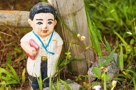Old statue baby doll welcome to thailand in garden