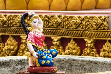 Religious statue at fountain, Thailand. Mother Earth Squeezing Her Hair Stockfoto - 129390931