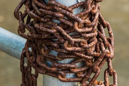 Old rusty chains on a steel pole Stockfoto - 129390731