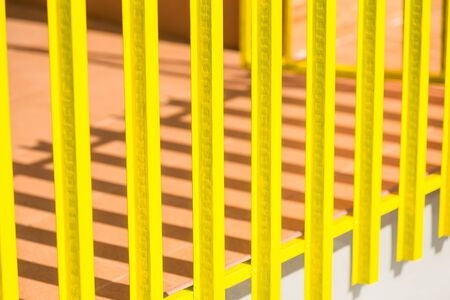 Yellow wooden fence and shadows from the sun light Stockfoto
