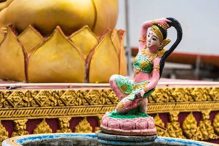 Religious statue at fountain, Thailand. Mother Earth Squeezing Her Hair Stockfoto - 129390653