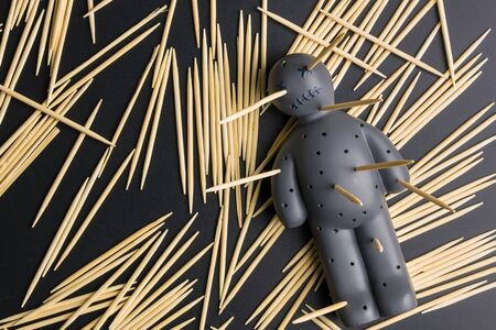 Voodoo doll with pins stuck into it on a black background with dramatic lighting
