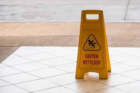 warning beware accident concept, The image of yellow caution wet floor plastic sign put on the concrete floor