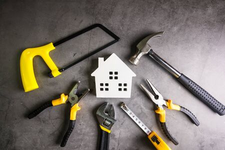 Wooden house and construction tools on stone pattern background with copy space.Home Repair concept, Repair maintenance concept, Renovation concept