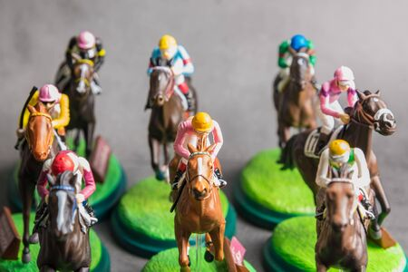 Galloping jockeys and race horses toy competing for position.Concept to compete for victory Stockfoto