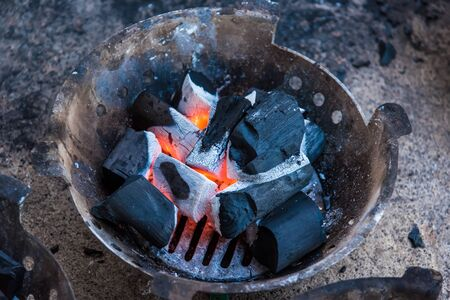 Closeup of flames erupted from black charcoal in the cooking stove 版權商用圖片