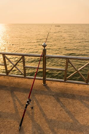 Fishing rod standing-up on the cement bridge by the sea during the sunset